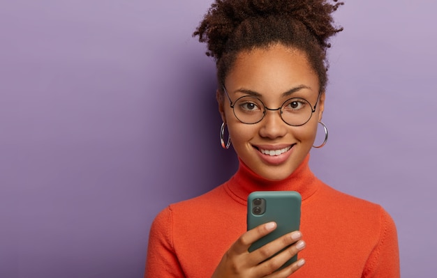 Headshot of lovely curly dark skinned woman uses mobile phone, smiles pleasantly, wears round spectacles, orange jumper, isolated on purple wall. technology, chatting concept Free Photo