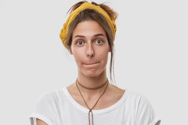Выстрел в голову привлекательной женщины, которая сжимает губы, смущает выражение лица, выглядит, носит желтый головной убор на голове Бесплатные Фотографии