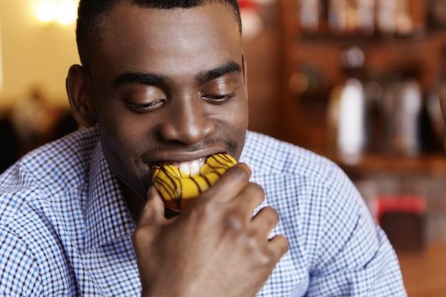 Выстрел в голову привлекательного молодого афро-американского бизнесмена, кусающего пончик Бесплатные Фотографии