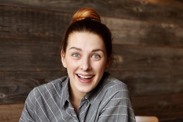 表情に驚いたカフェに座っている髪のお団子と魅力的な若い赤毛の女性のヘッドショット 無料写真
