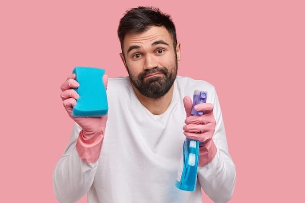 Выстрел в голову бородатого молодого европейца с густой бородой, в резиновых перчатках и белом повседневном джемпере, выглядит бессмысленным Бесплатные Фотографии