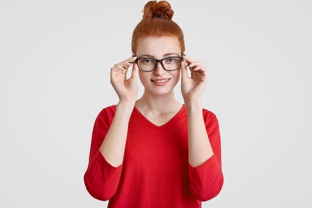 Выстрел в голову красивой веснушчатой молодой европейской женщины в очках, с нежной улыбкой, одетый в красный свитер Бесплатные Фотографии