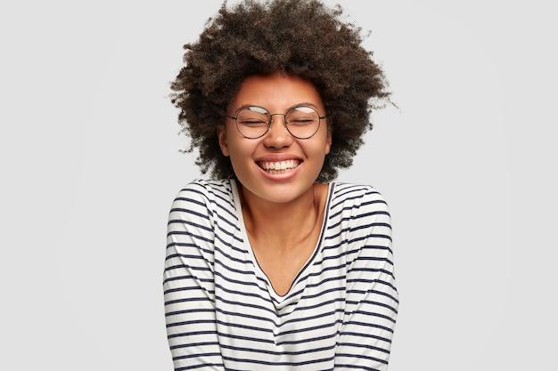 Выстрел в голову красивой улыбающейся смешной темнокожей женщины со стрижкой в стиле афро, над чем-то смеющейся, закрытой от удовольствия глазами, одетой в полосатый свитер, изолированной над белой стеной. счастье Бесплатные Фотографии