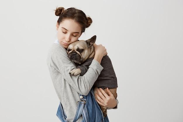 Выстрел в голову кавказской женщины с закрытыми глазами, держа ее прекрасный питомец как ребенок расслабляющий вместе. нежные эмоции милой девушки, обнимающей ее маленькую собаку, одетую в свитер. уход, концепция любви Бесплатные Фотографии
