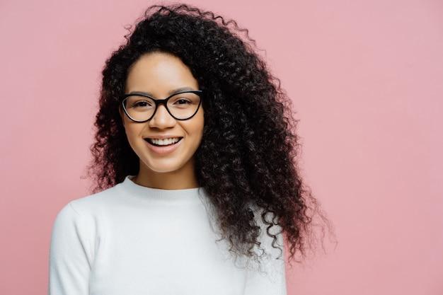 Выстрел в голову очаровательной молодой женщины с афро прической, приятно улыбается в камеру Premium Фотографии