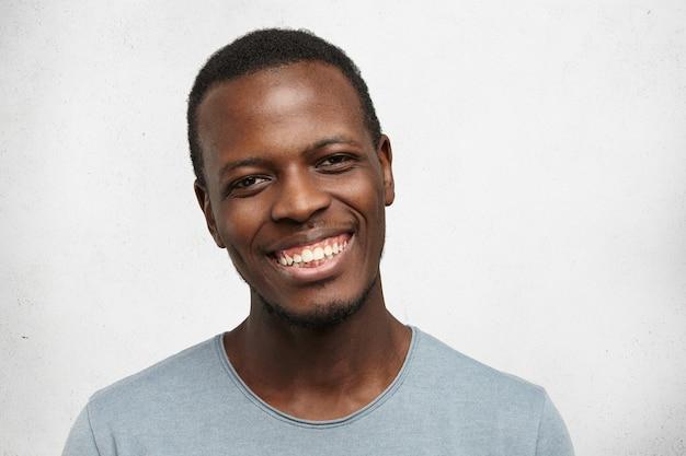 Headshot красивый молодой афро-американских мужчин, глядя с широкой дружеской улыбкой, наслаждаясь хорошим днем и свободное время в помещении. черный человек чувствует себя счастливым и беззаботным, отдыхая дома Бесплатные Фотографии