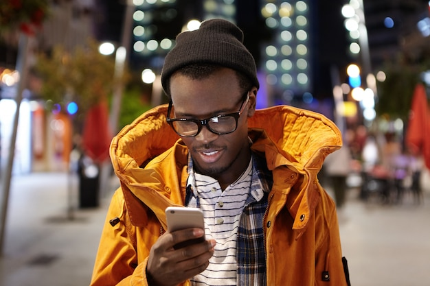 ハンサムな若いアフロアメリカン学生の夜の街を歩き、携帯電話を持って、都市のwifiを使用して、ソーシャルメディアで写真を閲覧するのヘッドショット。現代の技術とコミュニケーション 無料写真