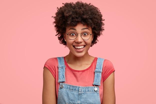 幸せなアフリカ系アメリカ人の女性のヘッドショットは、tシャツとデニムのダンガリーを着ています 無料写真