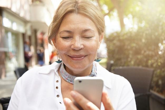 公正な髪と彼女の電子ガジェットの画面を見て美しい笑顔で幸せな高齢者のブロンドの女性のヘッドショット、屋外のカフェで座っているスマートフォンを使用してオンラインで彼女の子供たちと通信 無料写真