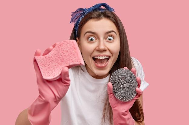 행복한 젊은 여성의 얼굴은 기쁨으로 응시하고, 입을 벌리고, 세균을 멀리하고, 스폰지로 먼지를 닦고, 고무 장갑, 머리띠를 착용하고, 가사를 마치고, 분홍색 벽 위에 포즈를 취합니다. 무료 사진