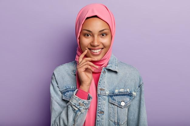 Снимок в голову красивой темнокожей арабской женщины, которая нежно держит руку у лица, широко улыбается, смотрит прямо в камеру Бесплатные Фотографии