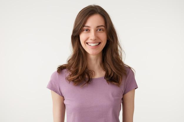 Выстрел в голову красивой привлекательной молодой леди, приятно улыбающейся, смотрящей прямо в камеру, в фиолетовой футболке Бесплатные Фотографии