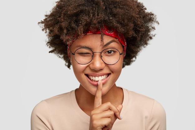 遊び心のある陽気な若いアフロ女性のヘッドショットは、前向きな表情で身振りをし、目を瞬きます 無料写真