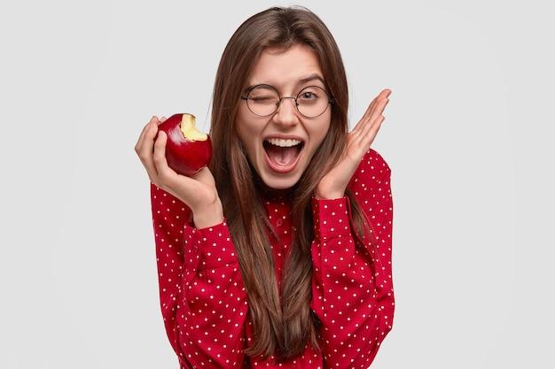 기뻐하는 젊은 여성의 얼굴 만은 눈을 깜박이고 머리 근처에서 손을 들고 신선한 사과를 물고 빨간 폴카 도트 블라우스를 입은 즐거운 표정을지었습니다. 무료 사진
