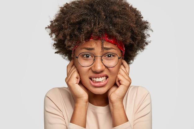 かなり不機嫌な女性のヘッドショットは人差し指で耳を閉じ、歯を食いしばり、不満に顔をしかめます 無料写真