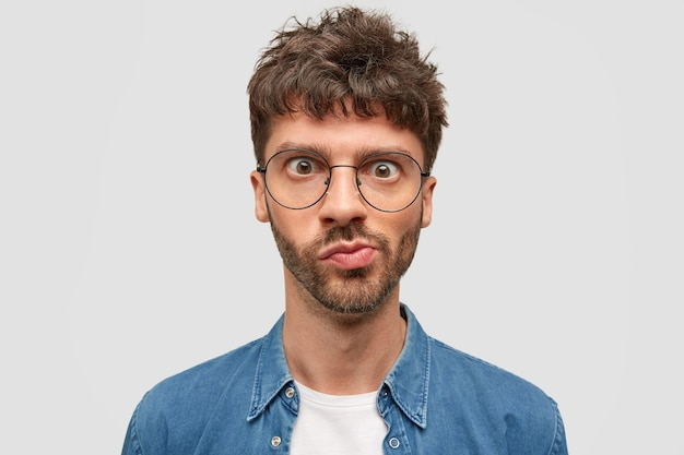 困惑したひげを生やした若い男のヘッドショットは、不思議に見え、唇を曲げ、目を大きく開いて、黒いウェーブのかかった髪をして、予期しないニュースを受け取り、何かについて考えます 無料写真