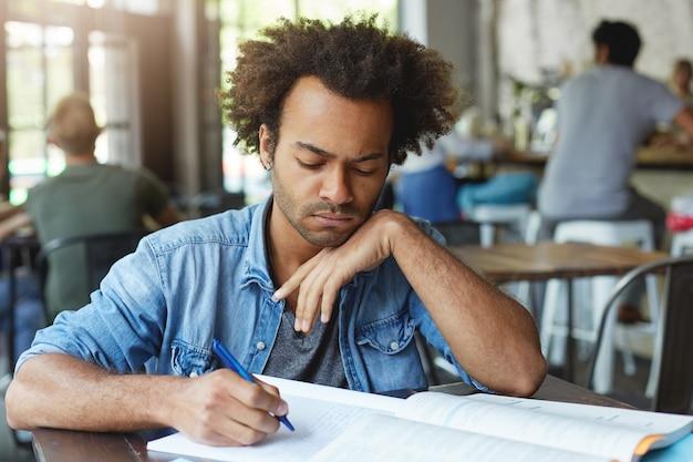 期末試験の準備、コピーブックでのメモ作成、表現に焦点を当てた、食堂やコワーキングスペースで勉強している青いスタイリッシュなシャツを着た深刻な浅黒い大学院生のヘッドショット 無料写真