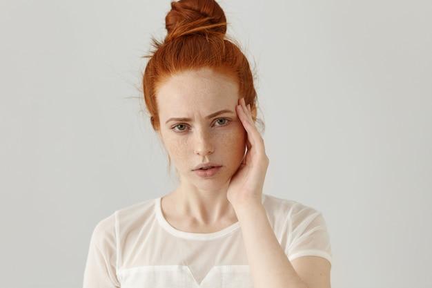 Выстрел в голову несчастной молодой рыжеволосой женщины с разбитым и болезненным выражением лица, нахмурившись, касаясь виска рукой, страдая от сильной головной боли или мигрени, сталкиваясь со стрессом на работе Бесплатные Фотографии