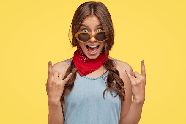 Il colpo alla testa del hipster femminile fresco provocatorio mostra il gesto della mano del rock n roll, esclama qualcosa ad alta voce Foto Gratuite