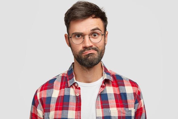 Primo piano del volto di un giovane con la barba lunga dispiaciuto esitante perplesso che increspa le labbra, ha un'espressione incerta, taglio di capelli alla moda, indossa una camicia a scacchi, isolato su un muro bianco. concetto di espressioni facciali Foto Gratuite