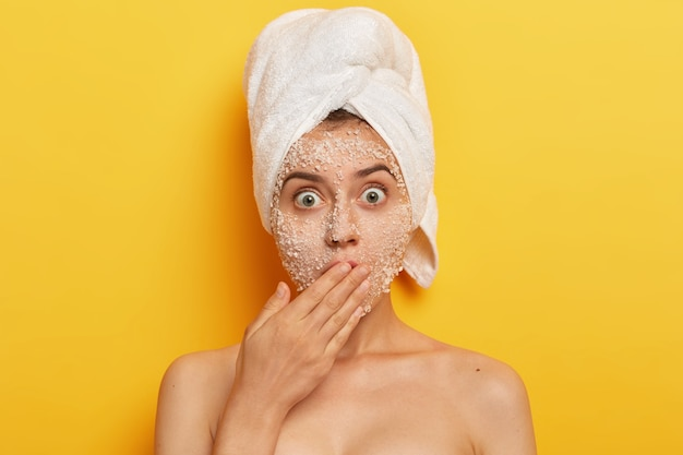 Headshot of stupefied young woman with natural scrub mask on face, gasps from fear, covers mouth with palm, reduces pimples stands shirtless exfoliates blackheads stares with popped out eyes Free Photo