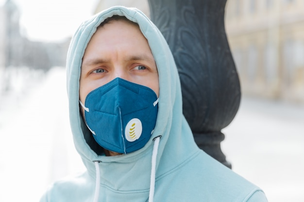 Headshot of thoughtful young man wears hood and respiratory mask, walks on street, protects from coronavirus, thinks about dangerous disease, being in danger. spreding covid-19 around world. Premium Photo