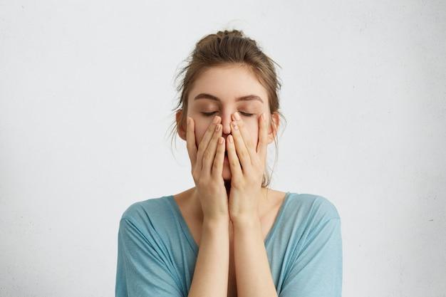 Headshot di giovane bella donna che chiude i suoi occhi che tengono le mani sul mento stanco Foto Gratuite