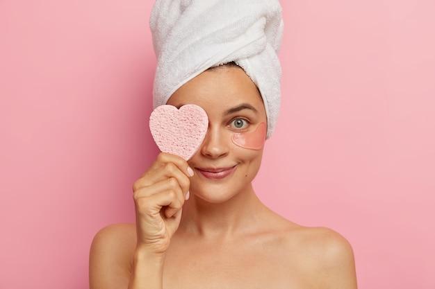 Il colpo alla testa della giovane donna applica le toppe sotto gli occhi per avere una pelle fresca e una prospettiva giovane, copre gli occhi con una spugna cosmetica, indossa un asciugamano bianco sulla testa dopo aver fatto la doccia, si prende cura della bellezza Foto Gratuite