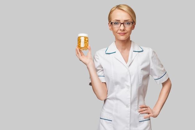 건강 관리 및 다이어트 개념-비타민 D 및 오메가 3 지방산 캡슐에 생선 기름을 들고 의사 영양사 또는 심장 전문의 프리미엄 사진