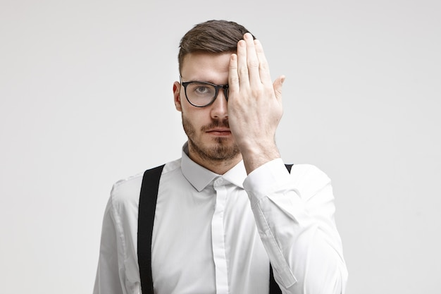 Health care, medicine, people, eyesight, optics, eyewear and contact lenses concept. serious young man with stubble covering one eye while having his eyes tested during eye vision examination Free Photo
