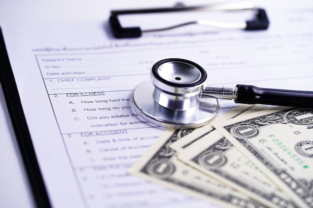 Health insurance accident claim form with stethoscope and us dollar banknotes Premium Photo
