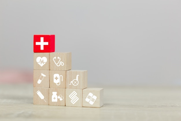 Health insurance concept,hand arranging wood block stacking with icon healthcare medical. Premium Photo