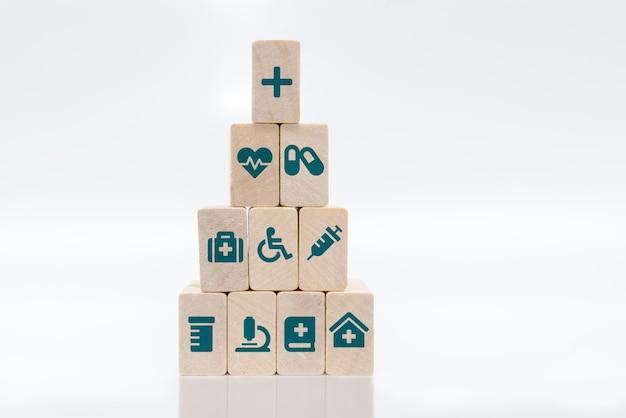 Концепция медицинского страхования. медицинские символы на деревянных блоках, сложенных в пирамиду на белом фоне. Premium Фотографии