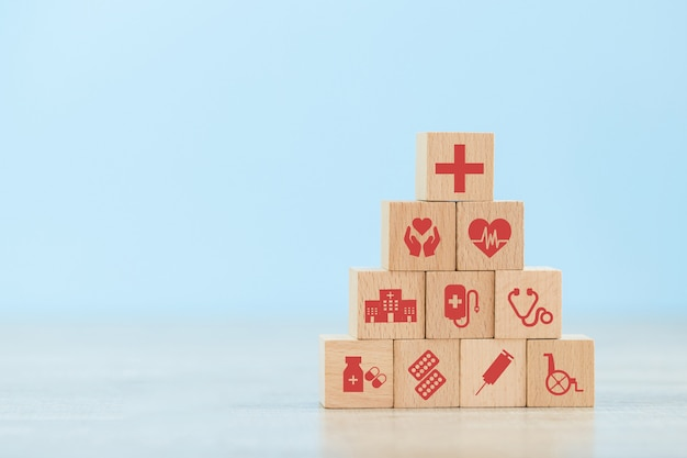 Health insurance wood block stacking with icon healthcare medical. Premium Photo