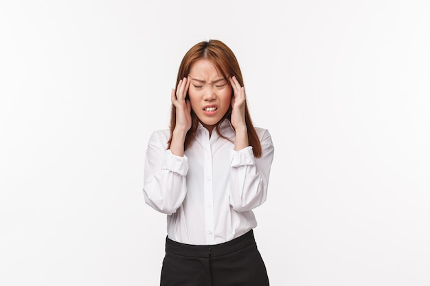 Health, medical care and people concept. portrait of asian woman in office outfit fill ill, touching temples and grimcaing from pain as suffering huge terrible headache, migraine, white wall Premium Photo