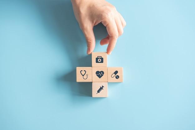 Концепция медицинской страховки здоровья, рука аранжируя деревянный куб с медицинским символом на пастельной голубой предпосылке, космосе экземпляра. Premium Фотографии