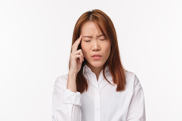 Health, midicine and people concept. close-up portrait of tired and dizzy young asian woman suffering headache, close eyes and touch temple, grimace painful feeling, have migraine, Premium Photo