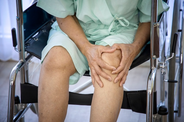 Концепция проблемы здоровья; старая женщина страдает от боли в коленях и ждет встречи с врачом в больнице. Premium Фотографии