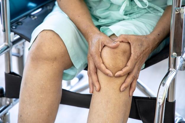 Концепция проблемы здоровья; старая женщина страдает от боли в колене в больнице. Premium Фотографии