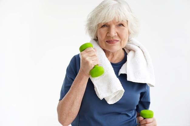 Здоровье, благополучие, активность, зрелость и возрастное понятие. жизнерадостная пожилая женщина на пенсии тренируется в помещении с белым полотенцем на шее, тренируется с парой зеленых гантелей и улыбается Бесплатные Фотографии