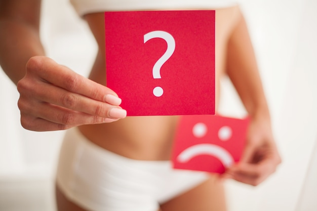 Health. woman body in underwear with question card near belly Premium Photo