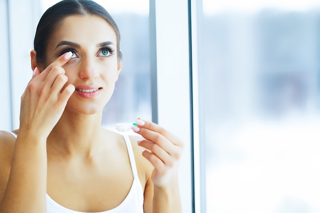 Health. young woman apply eye drops. fresh view. portrait of a beautiful woman with green eyes. Premium Photo