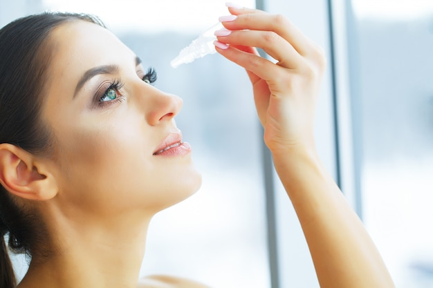 Health. young woman apply eye drops. fresh view. portrait of a beautiful woman with green eyes Premium Photo