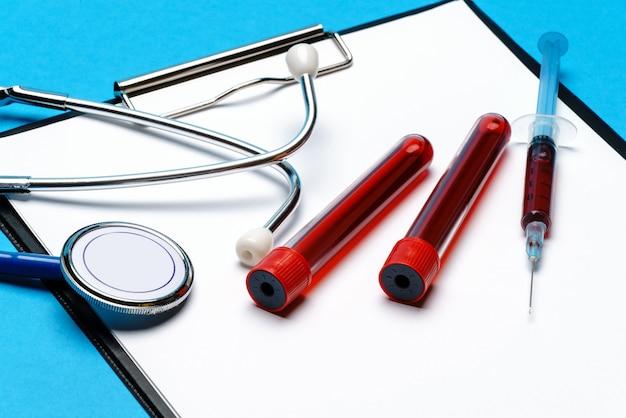ヘルスケアの概念-聴診器、血液検査管、注射器、空白のシート付きクリップボード。 Premium写真