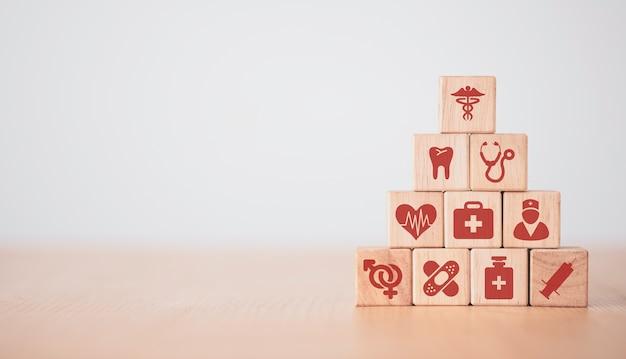 Концепция здравоохранения и больницы, рука кладет и укладывает кубики деревянных блоков, которые печатают значки здравоохранения экрана на столе с копией пространства. Premium Фотографии
