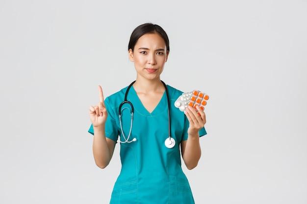 Медицинские работники, предотвращение вируса, концепция карантинной кампании. неохотно и разочарованно азиатская женщина-врач, врач неодобрительно трясет пальцем и ругает пациента за прием лекарств Premium Фотографии
