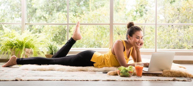 Healthy asian woman lying on the floor eating salad and looking at laptop computer Premium Photo