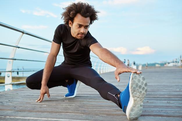 健康的なアスリートの浅黒い肌の少年は、午前中に木製のプラットフォームでストレッチします。彼の足を温めるふさふさした髪型を持つスポーティな男性 無料写真
