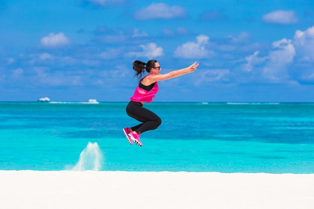 Healthy athlete woman working out doing exercise on tropical white beach Premium Photo