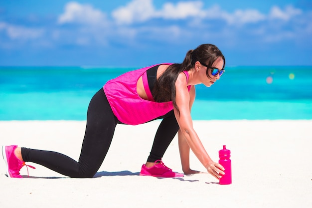 Healthy athlete woman working out doing exercise on white beach Premium Photo